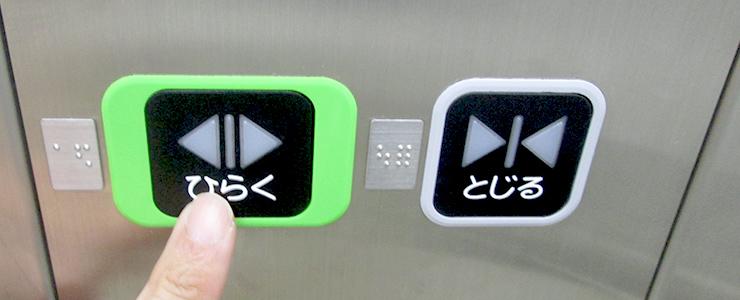 エレベーターでドアサポートをする男性