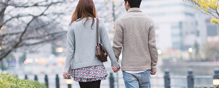仲良く手を繋いで歩くカップル