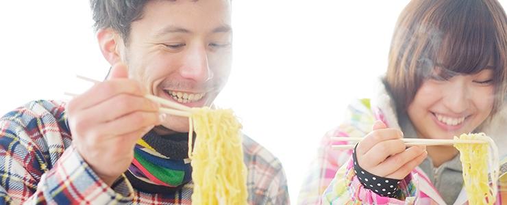 美味しそうにラーメンを食べる男女