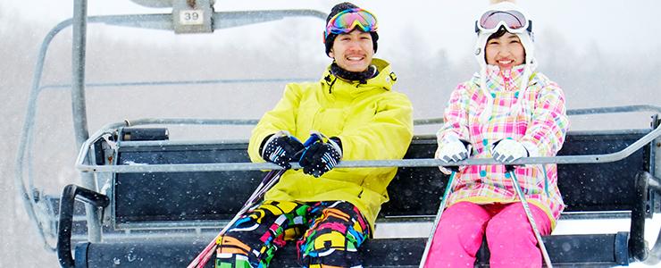 スキー場で楽しそうにリフトに乗るカップル