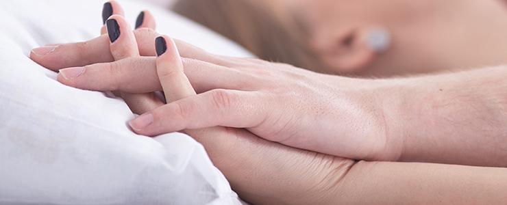 ホテルのベッドで手を重ねる男女
